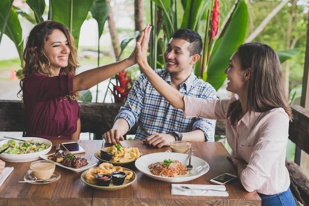 Hermosa mujer choca esos cinco con sus mejores amigos durante el almuerzo juntos en el café