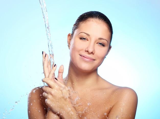 Hermosa mujer bajo un chorro de agua