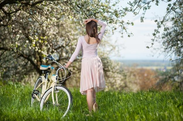 Hermosa mujer ciclista con bicicleta retro en el jardín de primavera