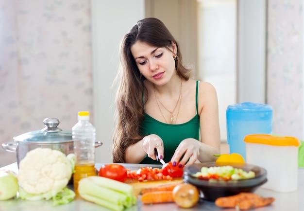 Hermosa mujer cocina ensalada vegetariana
