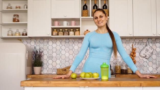 Una hermosa mujer en la cocina. la mujer es amable y sonriente. el concepto de nutrición adecuada, deportes y pérdida de peso en casa.
