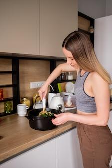 Hermosa mujer cocinando en cocina moderna