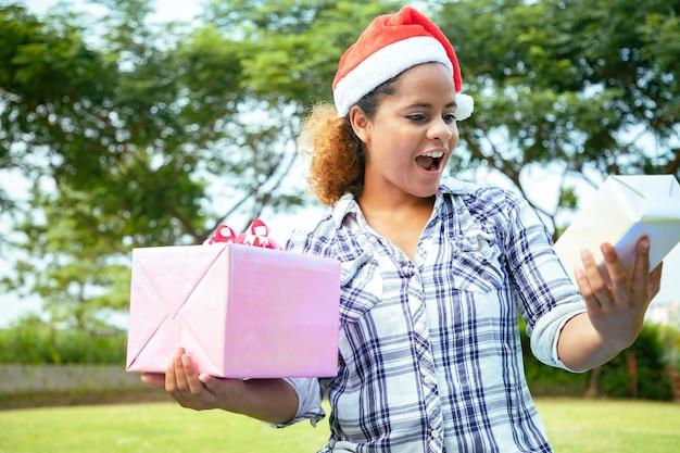 Una hermosa mujer cogidos de la mano con sombrero santy y selecta variedad de regalos en el jardín.