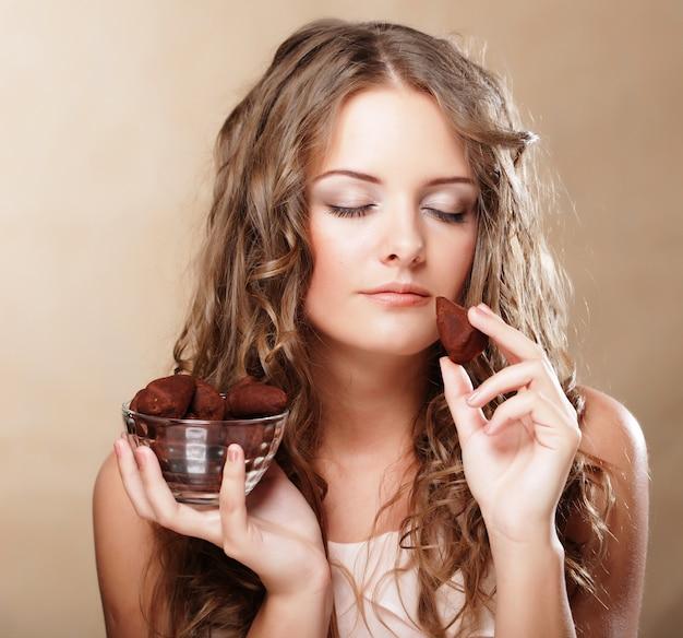 Hermosa mujer comiendo un bombón de chocolate