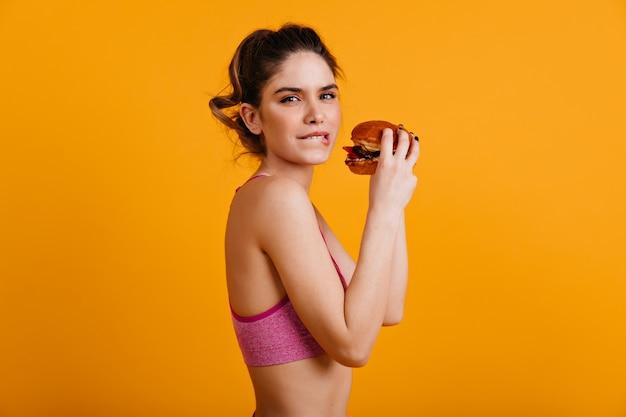 Hermosa mujer comiendo hamburguesa con queso