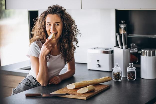 Hermosa mujer comiendo pan fresco en la cocina
