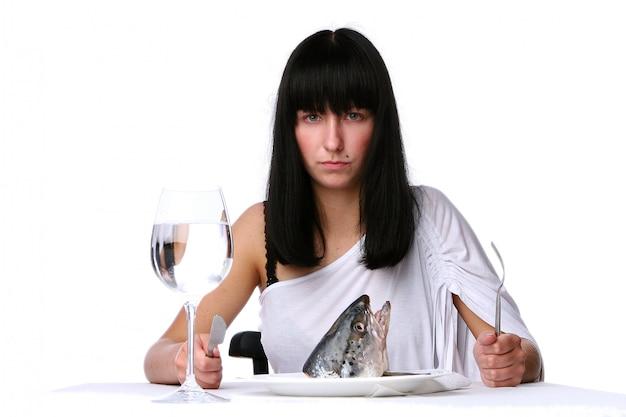 Hermosa mujer comiendo pescado fresco
