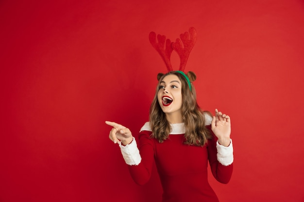 Hermosa mujer como ciervos de navidad aislado en concepto de pared roja