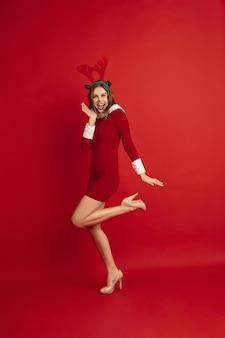 Hermosa mujer como ciervos de navidad aislado en concepto de superficie roja de vacaciones de humor de invierno de año nuevo
