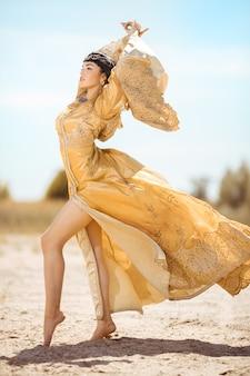 Hermosa mujer como la reina egipcia cleopatra en el desierto al aire libre