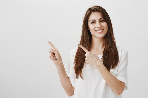 Hermosa mujer complacida apuntando a la esquina superior izquierda, sonriendo feliz como producto recomendado