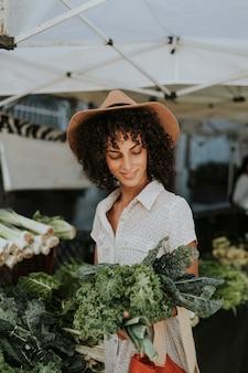Hermosa mujer comprando col rizada en un mercado de agricultores