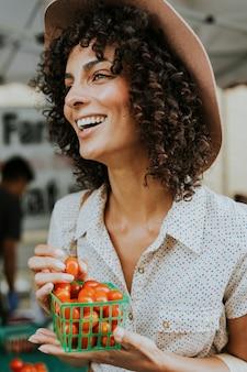 Hermosa mujer comprando tomates en un mercado de agricultores