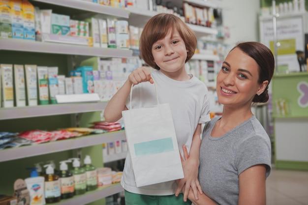 Hermosa mujer de compras en la farmacia con su pequeño hijo
