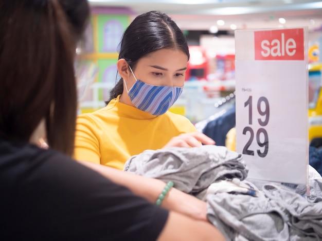Hermosa mujer está de compras en grandes almacenes durante la promoción de descuento de venta y usar máscara.