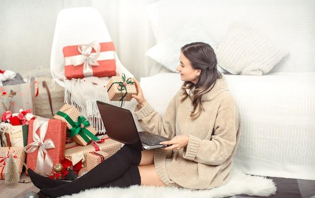 Hermosa mujer con computadora y regalos de navidad.