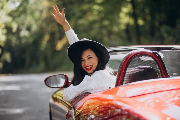 Hermosa mujer conduciendo cabrio rojo