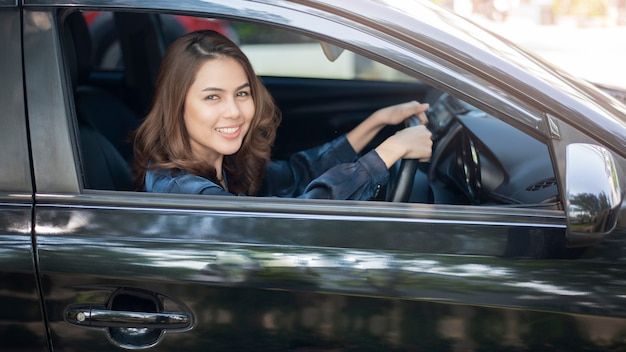Hermosa mujer está conduciendo su coche