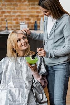 Hermosa mujer consiguiendo su cabello teñido por peluquero en casa