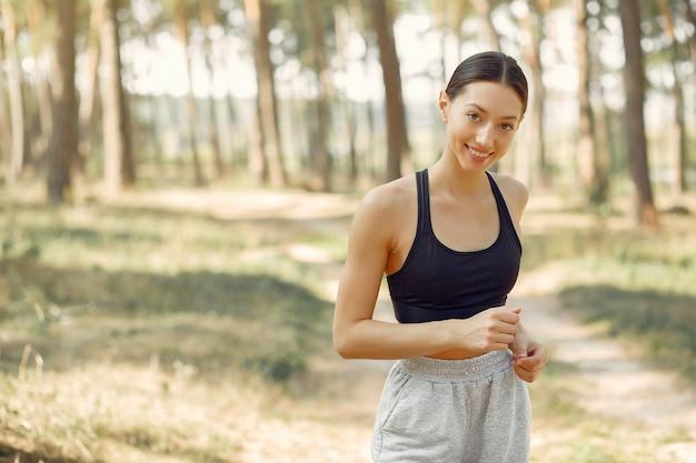 Hermosa mujer corre en un parque de verano