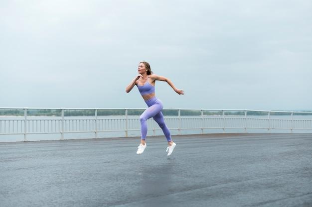 Hermosa mujer corriendo a lo largo del lago