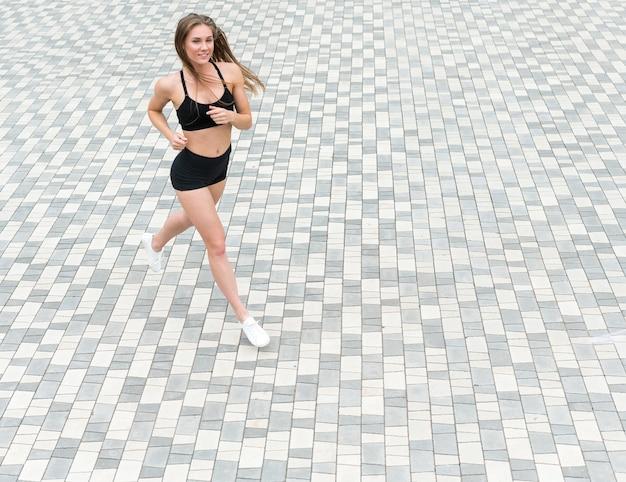 Hermosa mujer corriendo vista de ángulo alto al aire libre