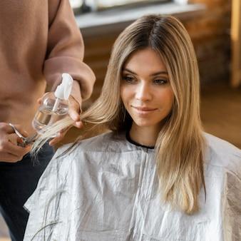 Hermosa mujer cortándose el pelo en casa por esteticista