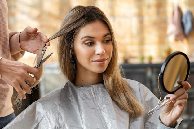 Hermosa mujer cortándose el pelo en casa por peluquero