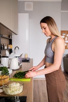 Hermosa mujer cortar eneldo en la cocina