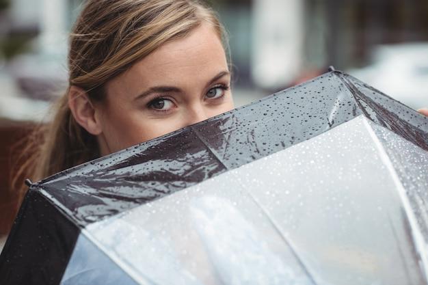 Hermosa mujer cubriendo su rostro con paraguas