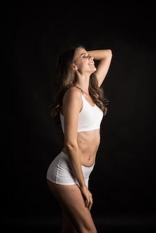 Hermosa mujer con cuerpo sano sobre fondo negro