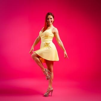 Hermosa mujer con cuerpo sano vistiendo un vestido bailando y girando sobre fondo rosa.