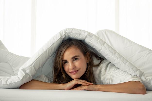 Hermosa mujer debajo de una manta blanca en la cama.