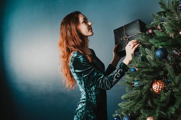 Hermosa mujer decorando el árbol de navidad