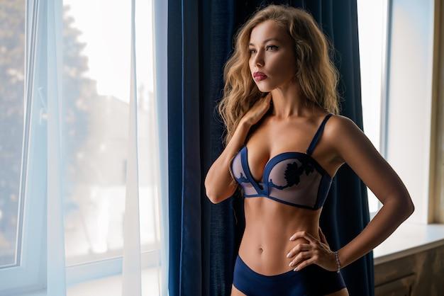 Hermosa mujer delgada en ropa interior en la ventana posando