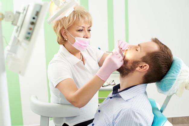 Hermosa mujer dentista atendiendo los dientes de un joven cliente masculino de la odontología moderna.