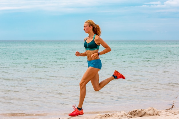 Hermosa mujer deportiva corriendo a lo largo de la hermosa playa de arena, estilo de vida saludable, disfrutando de unas activas vacaciones de verano cerca del mar