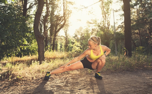 Hermosa mujer deportiva hace ejercicios deportivos en bosque