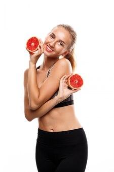 Hermosa mujer deportiva posando, sosteniendo pomelo