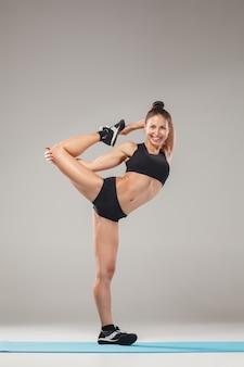 Hermosa mujer deportiva en pose de acróbata