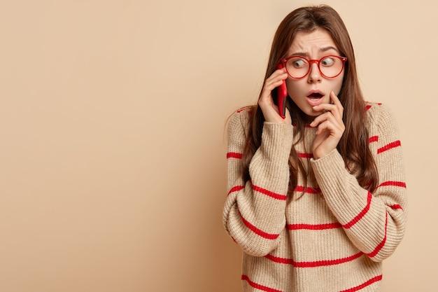Hermosa mujer desconcertada se siente avergonzada, hace una conversación telefónica, usa la aplicación en el teléfono celular, escucha noticias inesperadas, mira nerviosamente a un lado, aislado en una pared beige