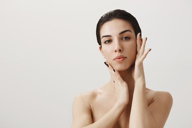 Hermosa mujer desnuda aplicar crema facial, tocando la cara suavemente