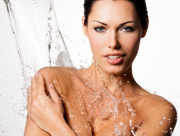 Hermosa mujer desnuda con cuerpo mojado y salpicaduras de agua
