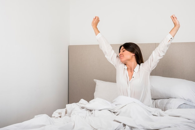 Hermosa mujer despertándose en su cama en el dormitorio.