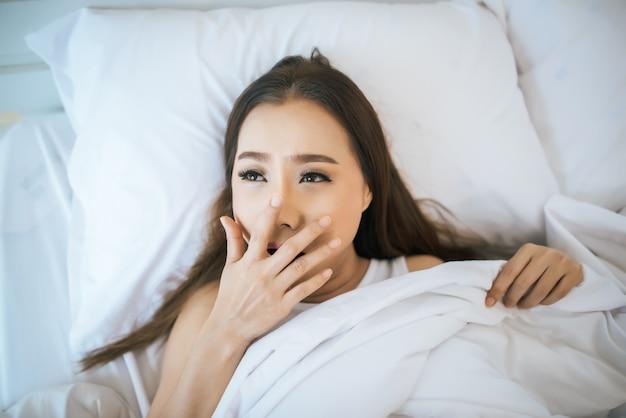 Hermosa mujer despertándose en su cama, perezosa por la mañana.