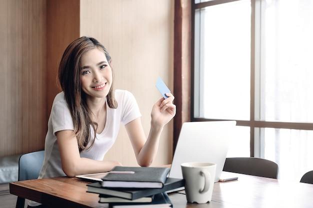 Hermosa mujer despreocupada en casual mostrando tarjeta de crédito