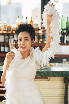 Hermosa mujer en disfraces y boa de pie con una flauta de champán en el bar