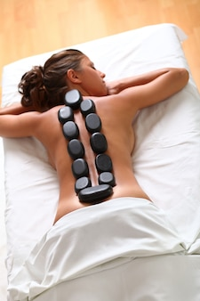 Hermosa mujer disfruta de spa con piedras