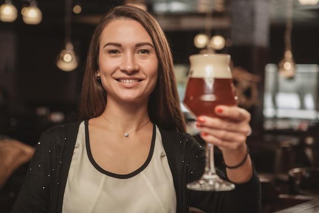 Hermosa mujer disfrutando de beber cerveza en el pub local