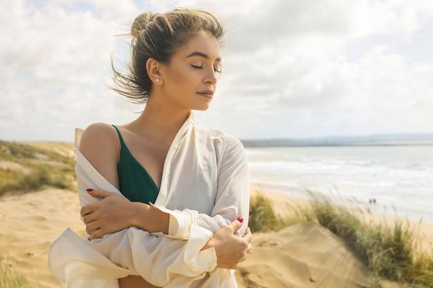 Hermosa mujer disfrutando de la brisa del mar mientras camina en la playa